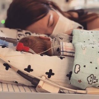 Slapende moeder aan het ziekenhuisbed.