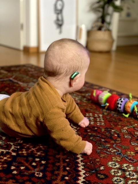 Dex in buikligging op de mat met zijn gehoorapparaten in.
