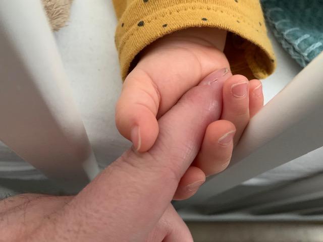 Vinger van Papa Niek in het kleine handje van baby Dex