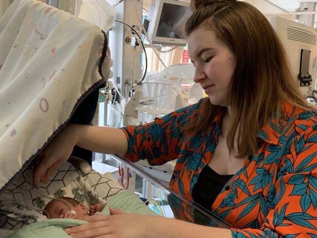 moeder naast babybed in het ziekenhuis