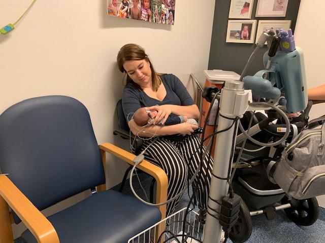 Gehoortest met baby op de arm bij mama